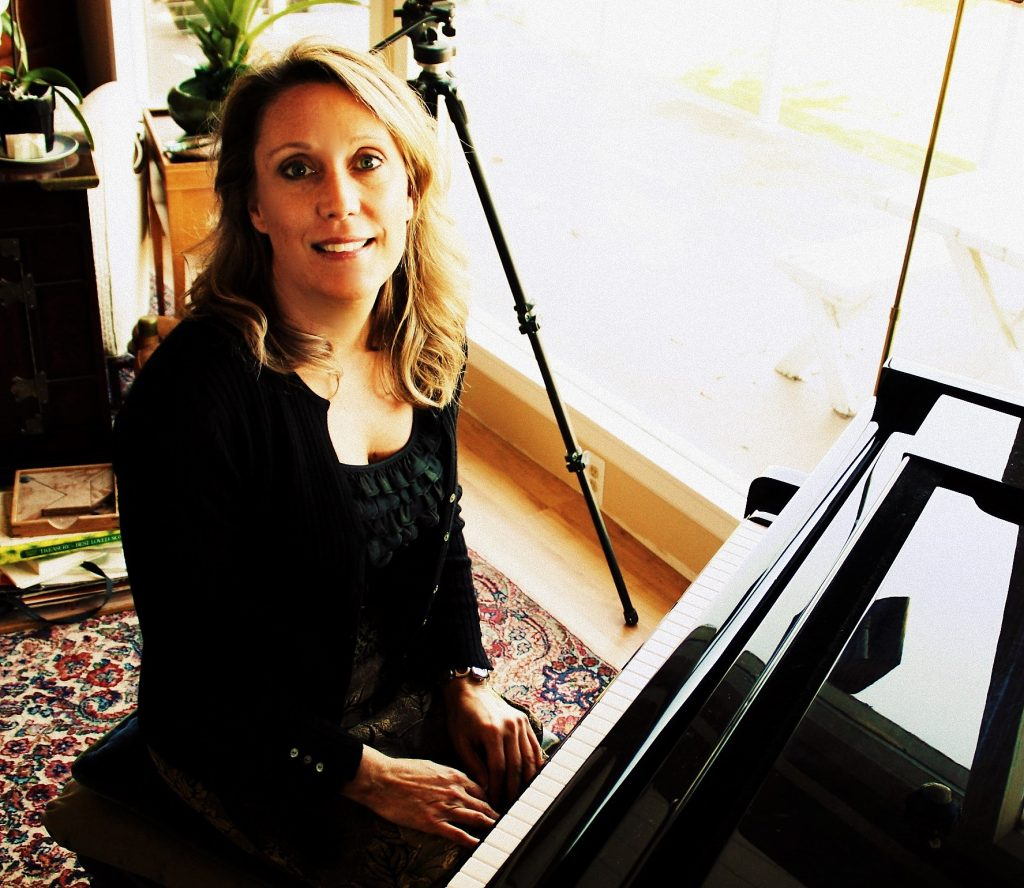 Smiling piano teacher at piano in Camano Island Studio
